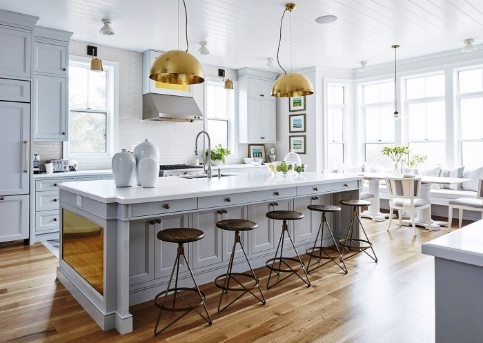 Full view of kitchen with warm hardwood flooring, clean white walls and brass accents